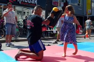 Ein Muay Thai Boxer lässt sich mit Freude von einem kleinen Mädchen verhauen